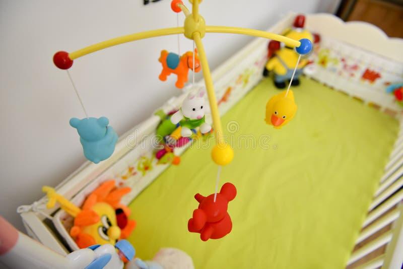 Dziecka łóżko polowe z kolorowy zabawek wieszać zdjęcia stock