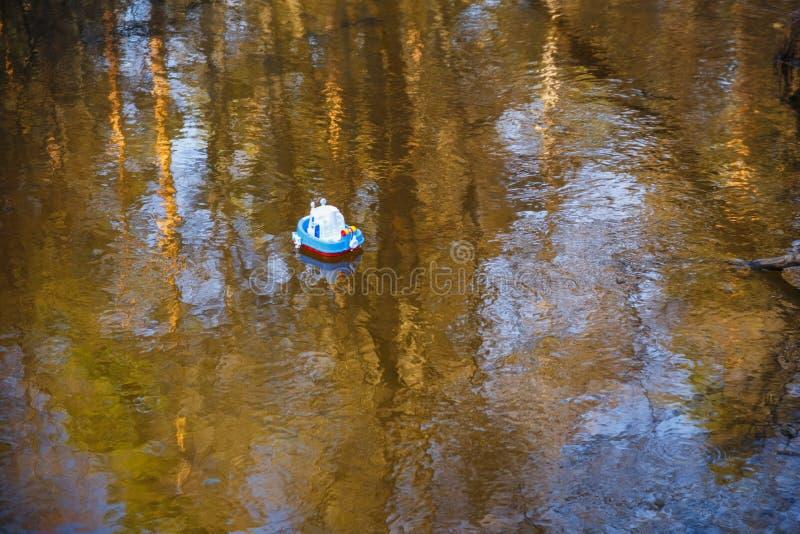 Dziecka łódkowaty błękit iść na złotej wodzie fotografia stock