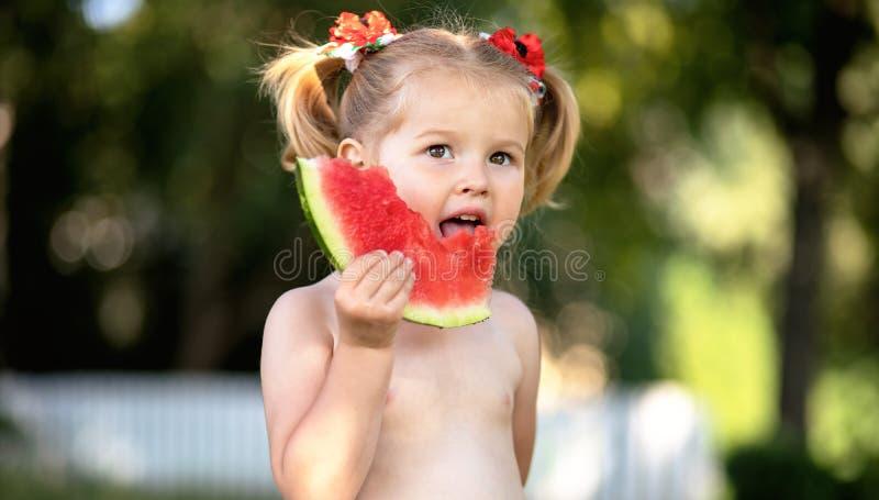 dziecka łasowania arbuz w ogródzie Dzieciaki jedzą owoc outdoors Zdrowa przekąska dla dzieci Mała dziewczynka bawić się w ogrodow fotografia royalty free