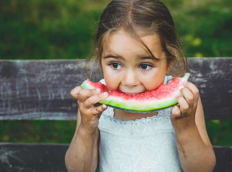 dziecka łasowania arbuz w ogródzie Dzieciaki jedzą owoc outdoors Zdrowa przekąska dla dzieci Piękny tło, emocji dziewczyna zdjęcie stock