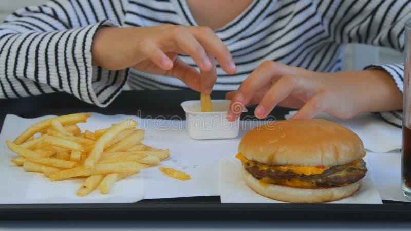 Dziecka łasowania hamburger w restauracji, dzieciak i fast food, dziewczyna Pije sok fotografia royalty free
