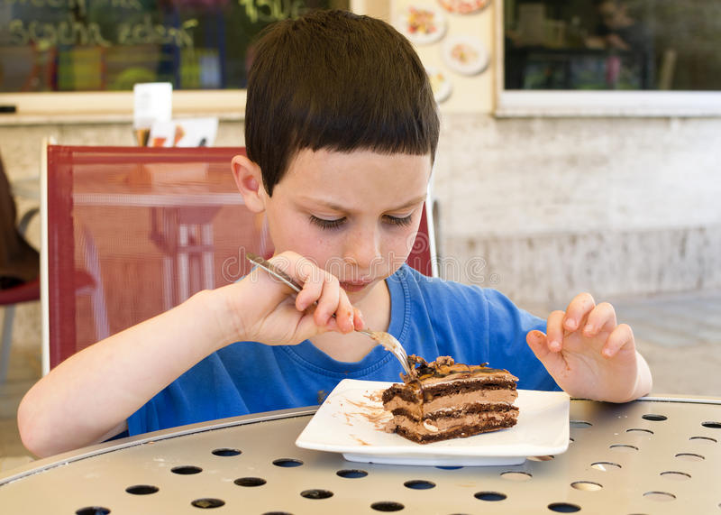 Dziecka łasowania tort w kawiarni fotografia royalty free