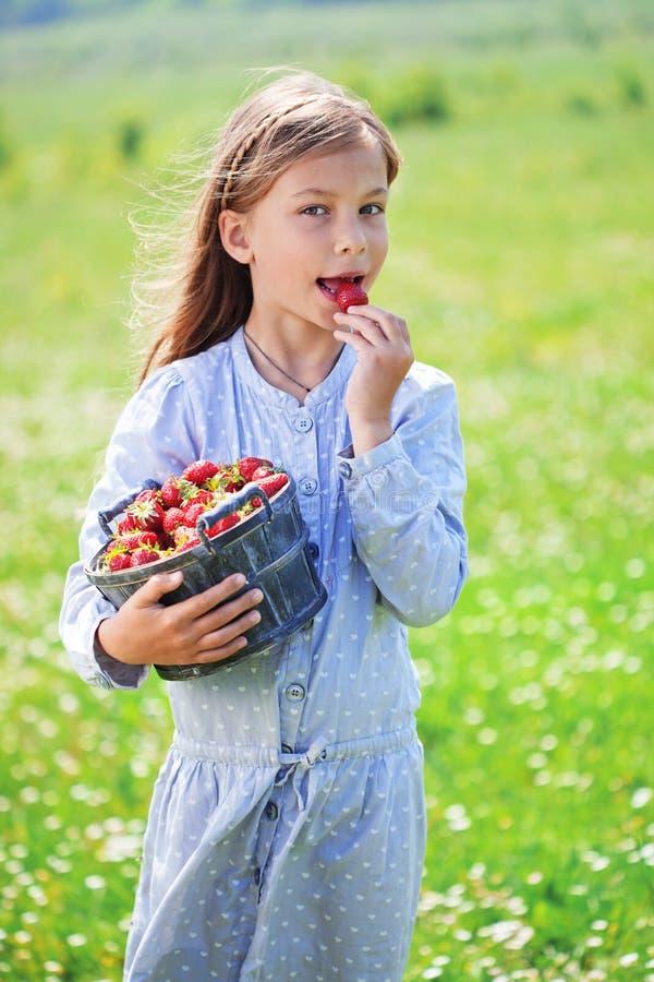 Dziecka łasowania truskawki w polu obraz royalty free