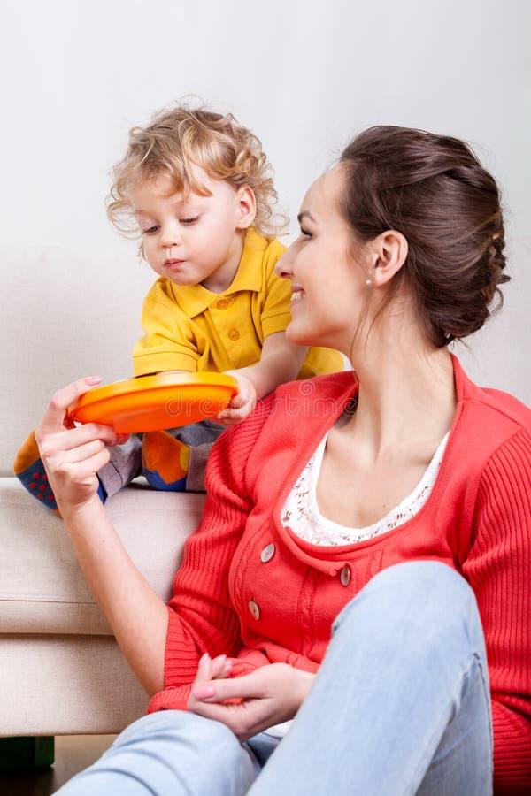 Dziecka łasowanie podczas gdy mama pomaga fotografia stock