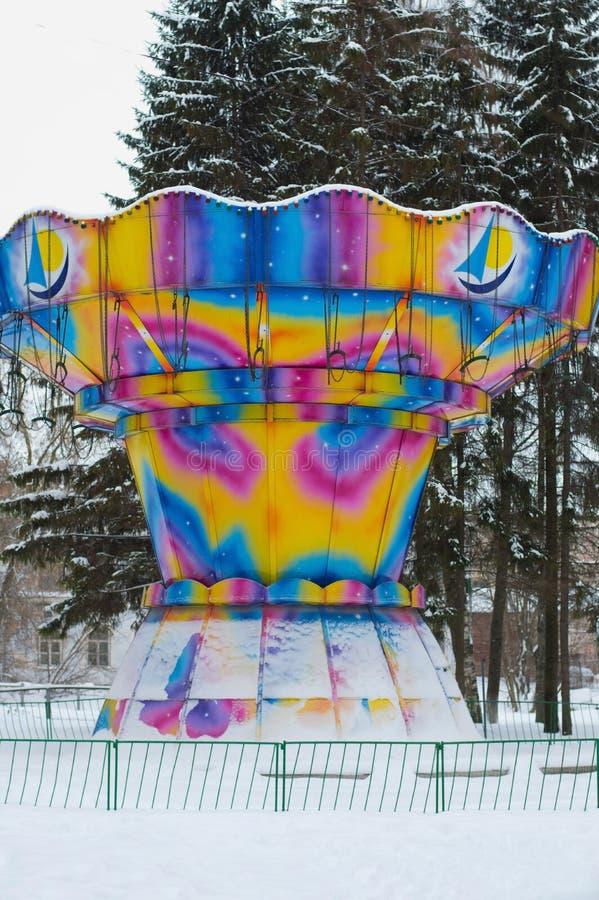 Dziecka carousel dla dzieci malował w jaskrawych kolorach w zima śniegu w parku obrazy royalty free