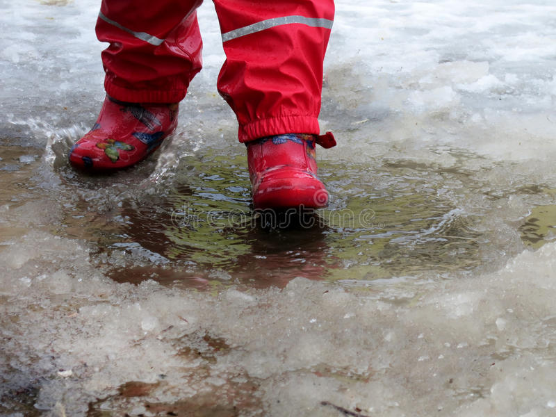 Dziecka doskakiwanie dla kałuż na drogach odtaja w końcówce zima obrazy royalty free