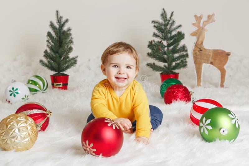 Dziecka dziecko w żółtego puloweru odzieżowym obsiadaniu na białym puszystym dywanik odświętności nowym roku lub bożych narodzeni zdjęcie stock