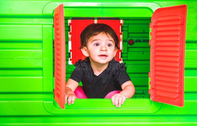 Dziecka inside zabawki domu domek do zabaw dziecka spojrzenie out okno fotografia stock