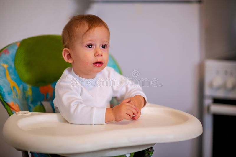 Dziecka karmienie Szczęśliwy dzieciaka obsiadanie na highchair obrazy royalty free