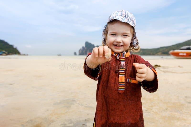 Dziecka kolekcjonowania skorupy na tropikalnej plaży obraz royalty free