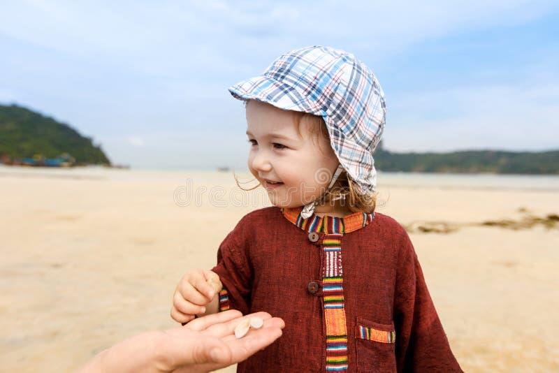 Dziecka kolekcjonowanie łuska na tropikalnej piaskowatej plaży i obrazy royalty free