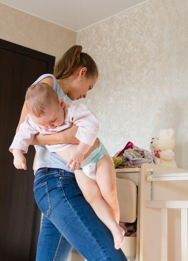 dziecka mienia mama Mama czyści dziecka odziewa zdjęcie stock