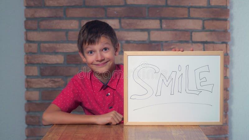 Dziecka obsiadanie przy biurka mienia flipchart z literowanie uśmiechem zdjęcia royalty free
