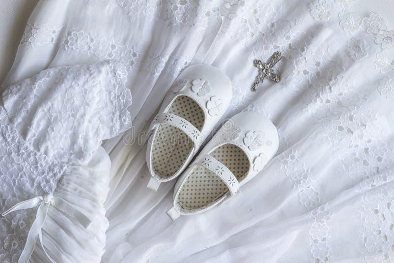Dziecka ochrzczenia koronki suknia, buty i kryształu przecinający breloczek na whit, zdjęcie royalty free