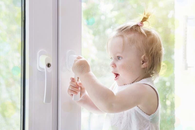 Dziecka okno z kędziorka zakończeniem up Dziecko przy nadokienny makro- Okno z kędziorkiem fotografia stock