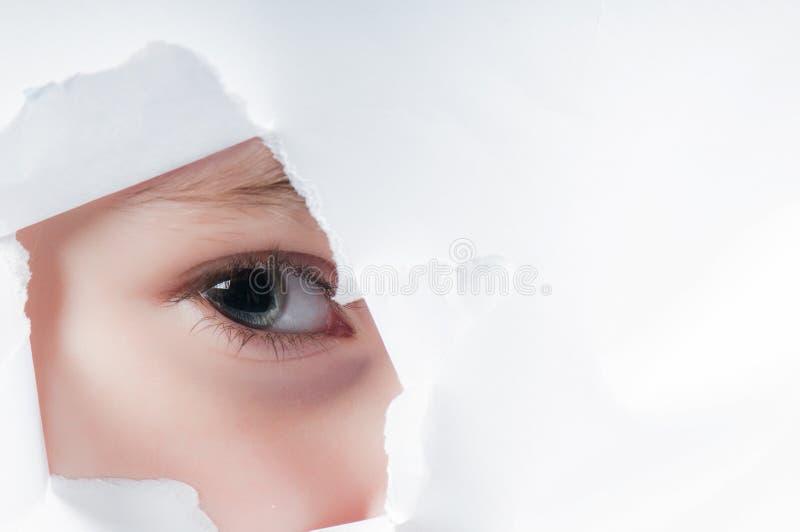 Dziecka oko patrzeje przez dziury w papierze fotografia stock