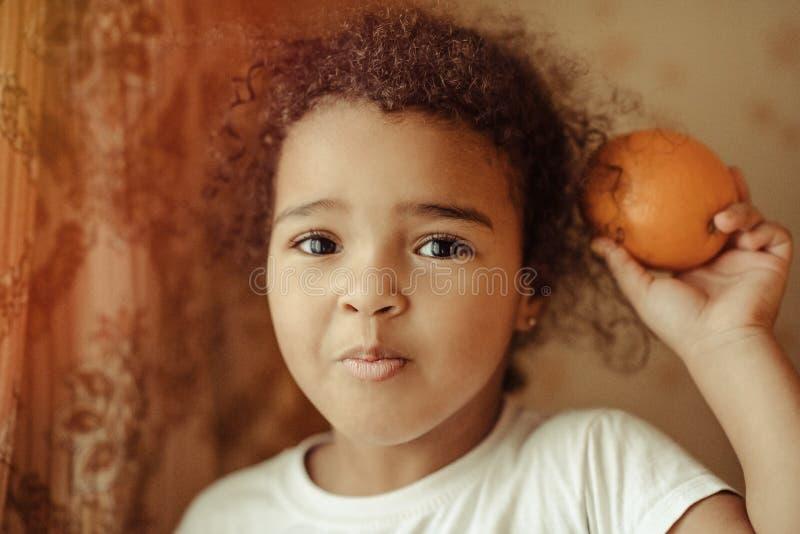 dziecka owocowej dziewczyny szczęśliwe domowe małe pomarańcze Szczęśliwa mała dziewczynka z owoc zdjęcia stock