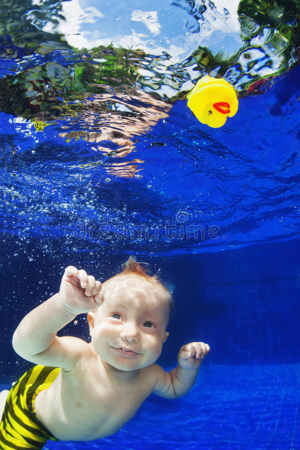 Dziecka pływać podwodny w błękitnym basenie dla kolor żółty zabawki zdjęcia stock