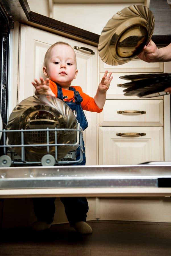 Dziecka pomagać rozładowywa zmywarka do naczyń obrazy stock