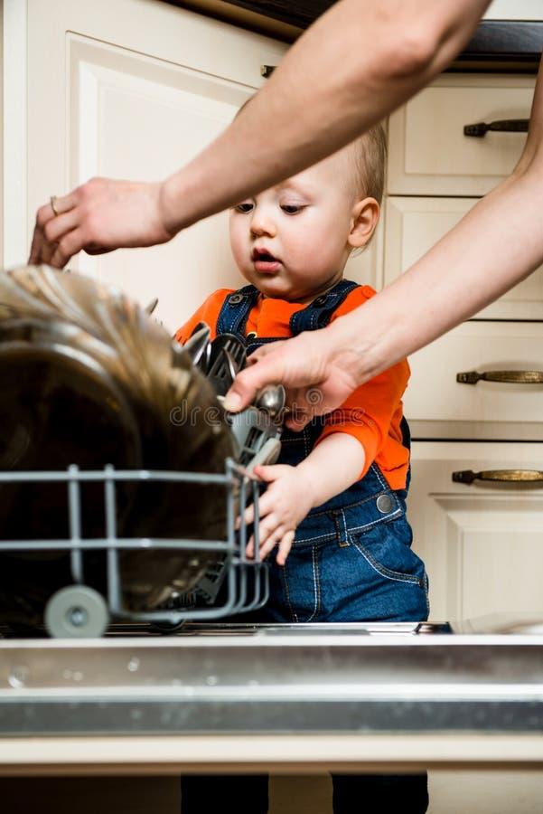 Dziecka pomagać rozładowywa zmywarka do naczyń zdjęcie royalty free