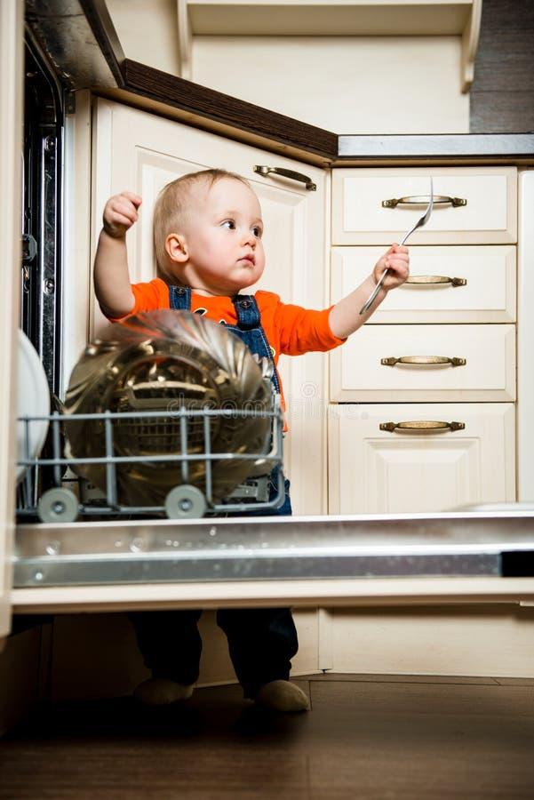 Dziecka pomagać rozładowywa zmywarka do naczyń fotografia royalty free