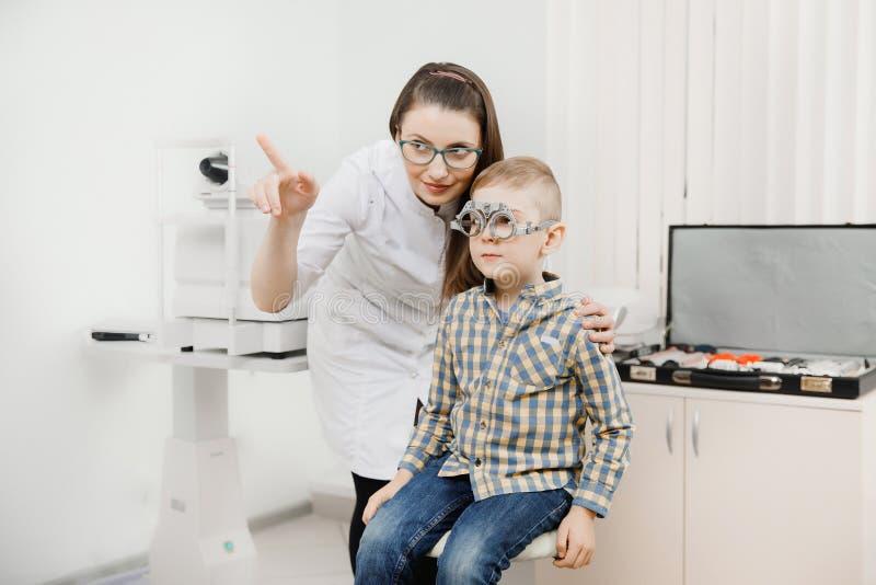 Dziecka przyjęcia lekarki oftalmolog wybiera szkła obiektyw, czeka oka widok zdjęcia royalty free