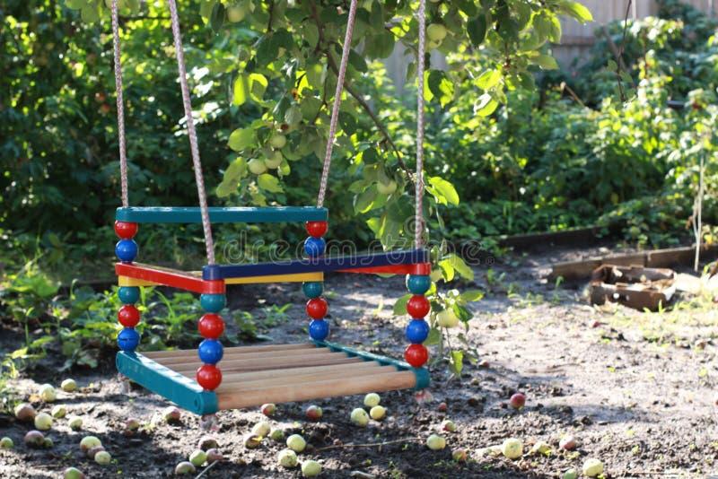 Dziecka ` s barwiąca huśtawka w podwórzu wioska dom zdjęcie stock