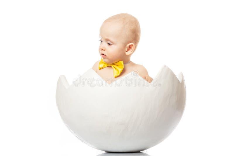 Dziecka ` s emocje dziecko z żółtym motylem w jajku na białym tle miła niespodzianka Śliczna chłopiec w jajecznej skorupie zdjęcie stock
