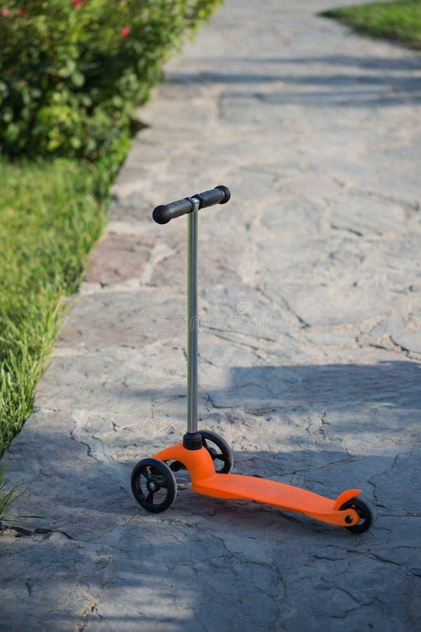 Dziecka ` s hulajnoga pomarańczowi stojaki na drodze Lato, odpoczynek, sport obrazy stock