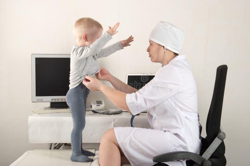 Dziecka ` s lekarka egzamininuje pacjentów w jego biurze Szczęśliwi dzieci kochają dobrego pediatra bardzo mocno Zamyka up caucas fotografia royalty free