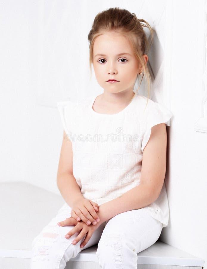 Dziecka ` s moda Piękna zadumana poważna blondynki dziewczyna siedzi i pozuje w biel ubraniach obraz stock