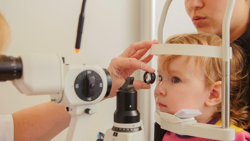 Dziecka ` s okulistyka - doktorski optometrist sprawdza wzrok przy małą dziewczynką obraz stock