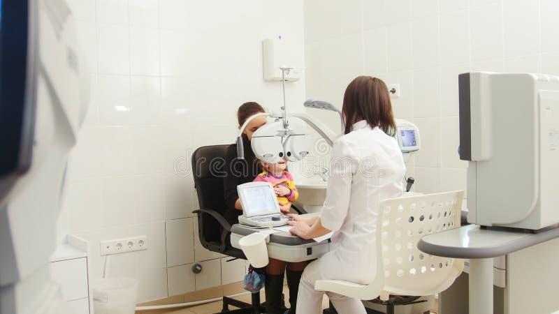 Dziecka ` s okulistyka - optometrist sprawdza małej dziewczynki ` s wzrok w klinice obrazy royalty free