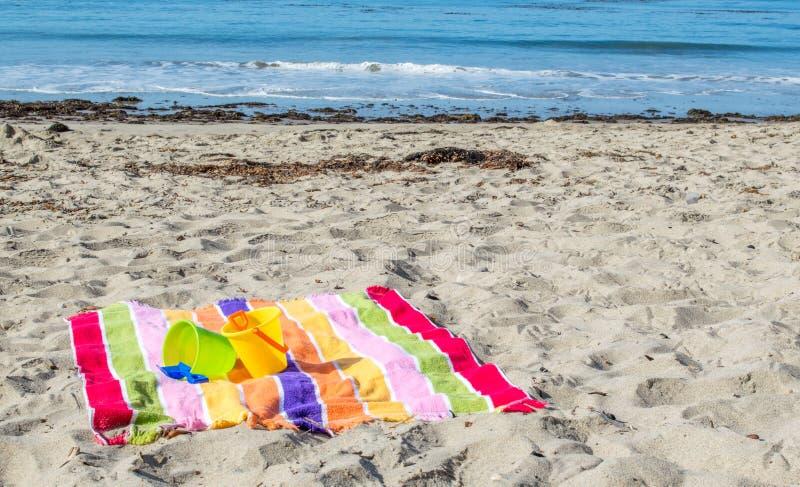 2 dziecka ` s piaska łopaty na pasiastym plażowym ręczniku przy oceanem i pails zdjęcia stock