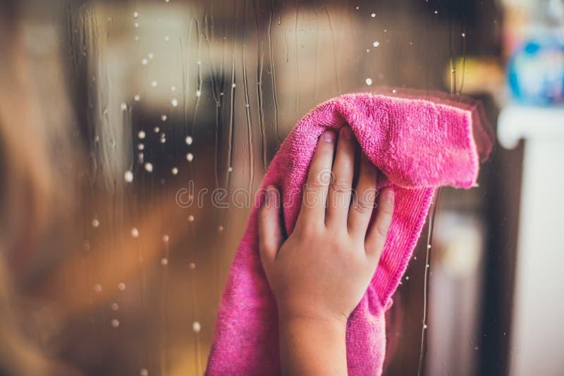 Dziecka ` s ręka wyciera okno obraz stock
