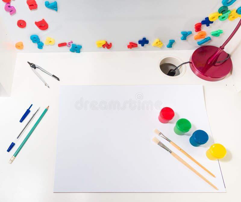 Dziecka ` s szkoły biurko z kolorowymi farbami, listy, liczby, pióro, ołówek, kompas, biurko lampa i biały prześcieradło papier, fotografia royalty free