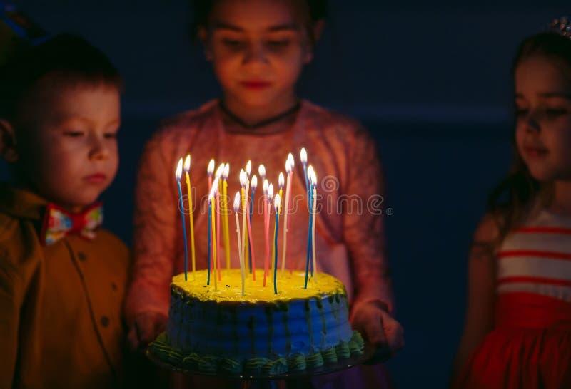 Dziecka ` s urodziny Dzieci blisko urodzinowego torta z ?wieczkami obrazy royalty free