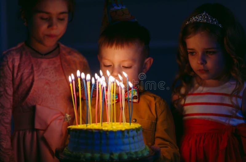 Dziecka ` s urodziny Dzieci blisko urodzinowego torta z ?wieczkami zdjęcia stock