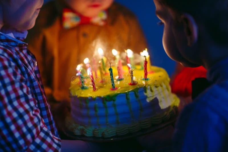 Dziecka ` s urodziny Dzieci blisko urodzinowego torta z ?wieczkami fotografia royalty free