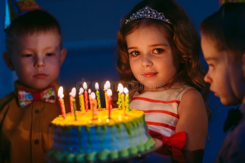 Dziecka ` s urodziny Dzieci blisko urodzinowego torta z ?wieczkami obrazy stock