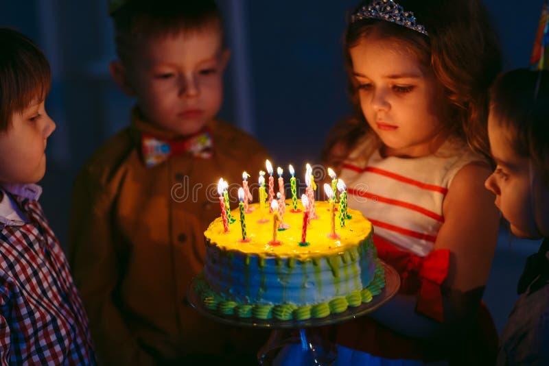 Dziecka ` s urodziny Dzieci blisko urodzinowego torta z ?wieczkami zdjęcie royalty free