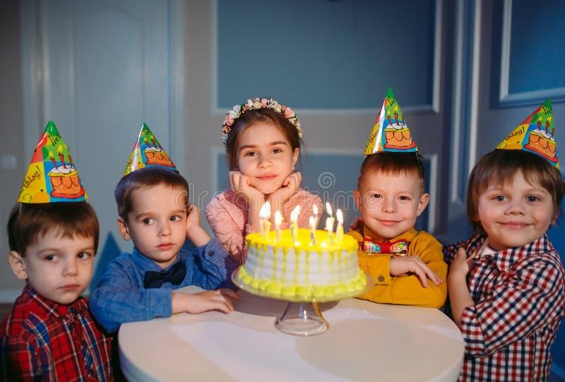 Dziecka ` s urodziny Dzieci blisko urodzinowego torta z ?wieczkami obraz stock