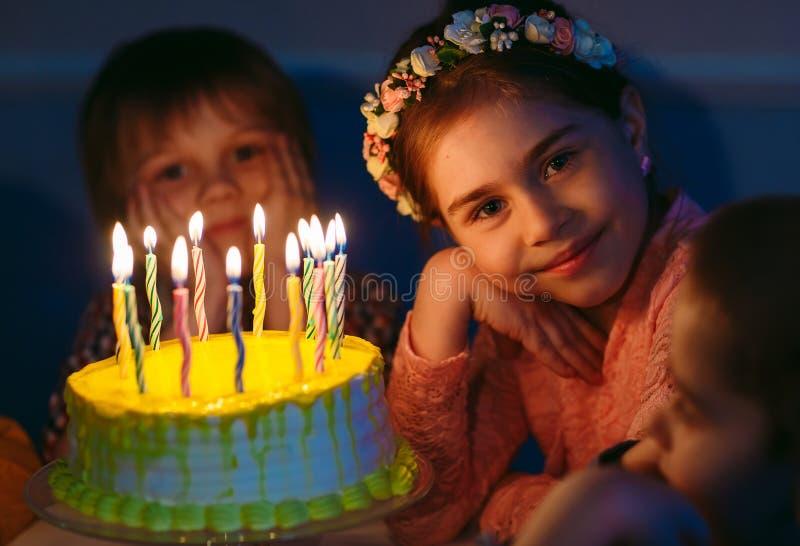 Dziecka ` s urodziny Dzieci blisko urodzinowego torta z ?wieczkami zdjęcie stock