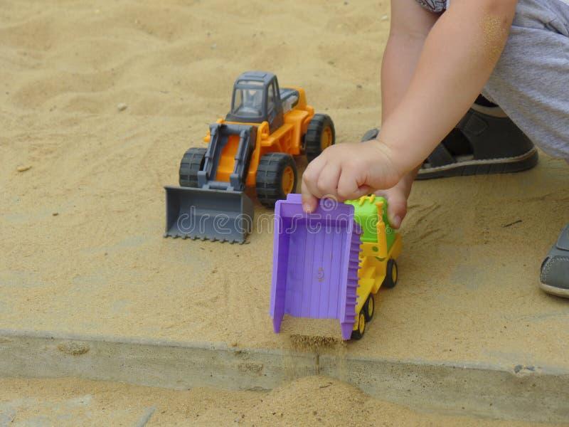 Dziecka ` s wręcza sztuce z zabawkami ciężarówkę i ciągnika fotografia royalty free