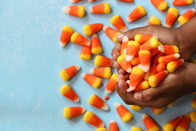 Dziecka ` s wręcza trzymać Halloweenowej cukierek kukurudzy, selekcyjna ostrość zdjęcia royalty free