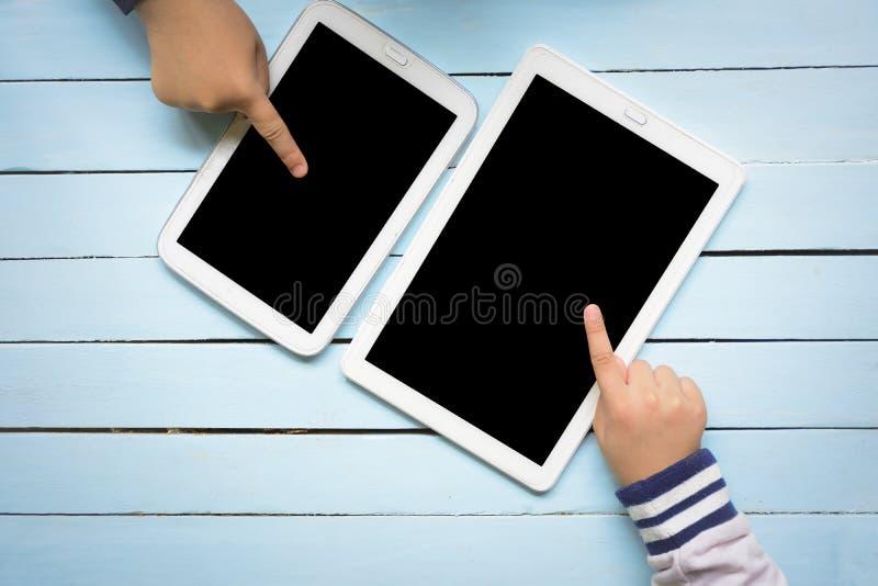 Dziecka ` s wręcza używać pastylka komputer na drewnianym błękita stole Odgórny widok i zbliża wewnątrz fotografia royalty free
