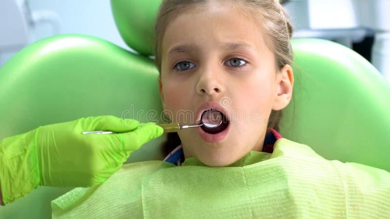 Dziecka stomatologist egzamininuje zęby z usta lustrem, rutynowy egzamin zdjęcia royalty free