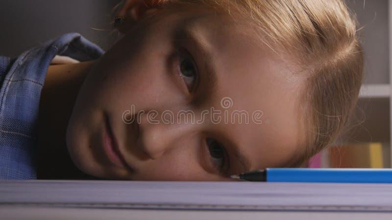 Dziecka studiowanie w nocy, Zanudzający dzieciak Pisze w zmroku, Męczący Smutny Studencki uczenie obraz stock