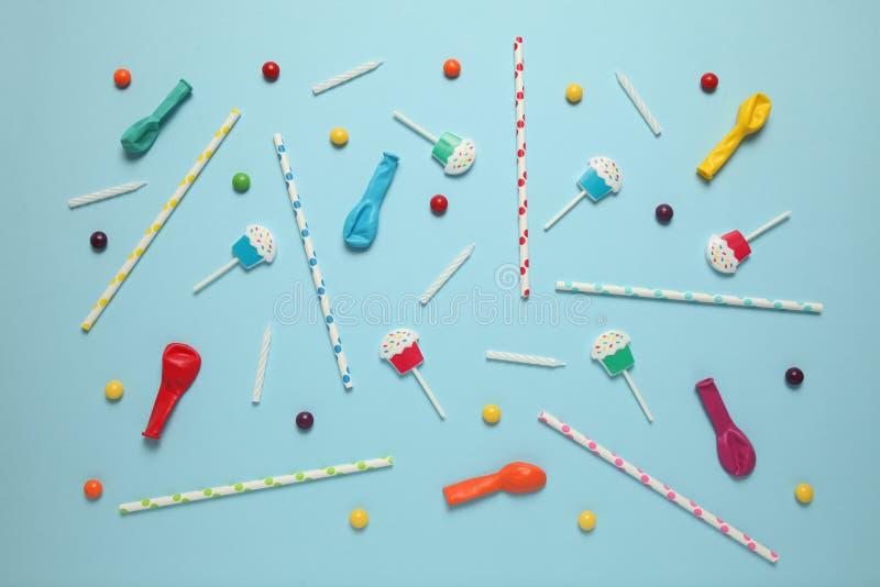 Dziecka urodzinowy błękitny tło Rozrzuceni kolorowi cukierki, pi?ki, ?wieczki i s?oma, zdjęcie royalty free