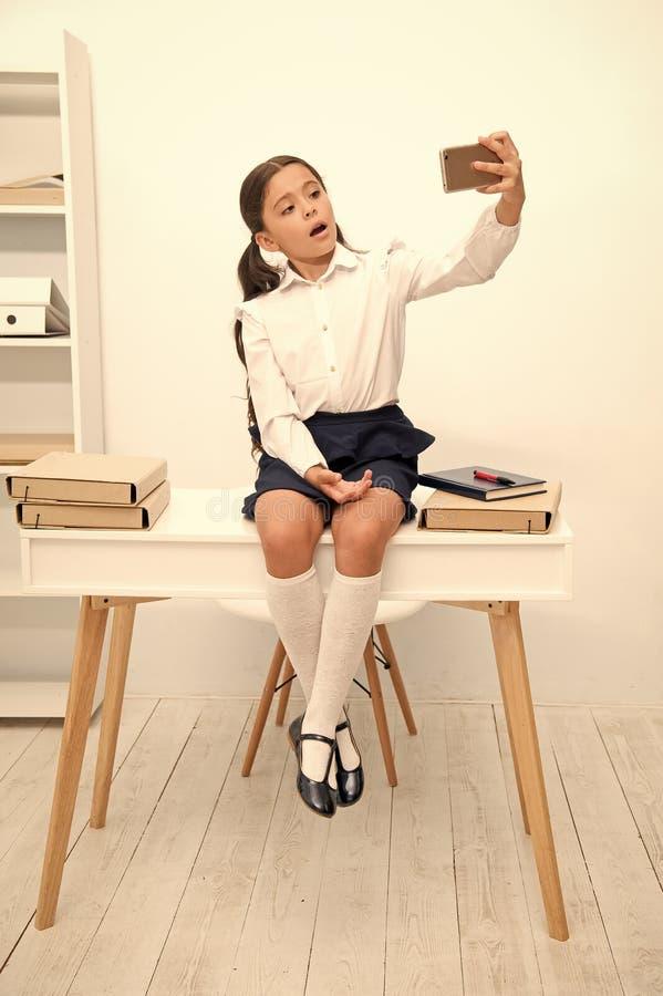 Dziecka vlogger strumie? online Dziecko mundurka szkolnego m?drze dzieciaka wideo konferencja podczas gdy siedzi st?? Dziewczyna  zdjęcie stock